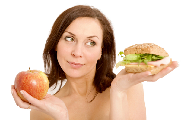 A woman holding an apple and a hamburger.